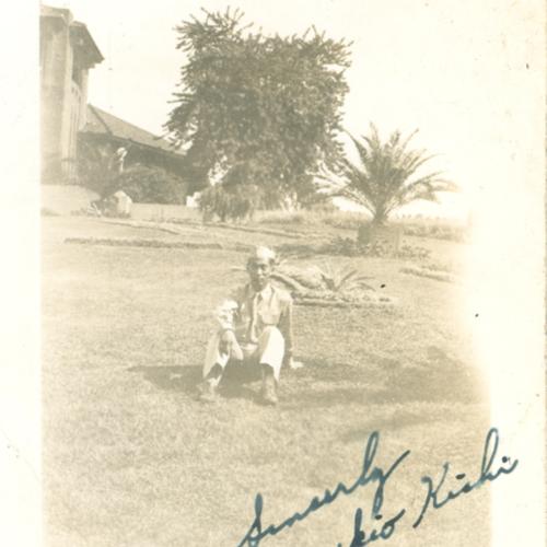 Yukio Kishi in uniform sitting in the grass