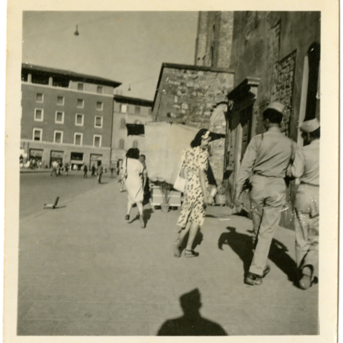 World War Two soldiers walking with a woman in a piazza