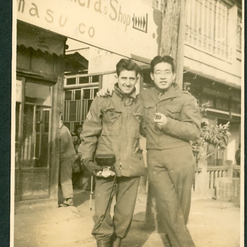 Two soldiers in front of a camera shop
