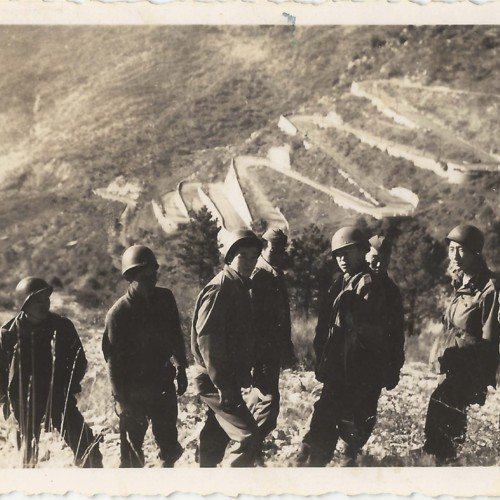 Six Japanese American soldiers on hilltop with switchback road in background