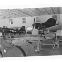 Gilbert T. Tanji album page 67. Military aircraft in airfield hangar