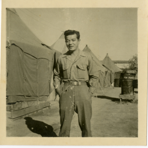 World War Two soldier posing outside of tents