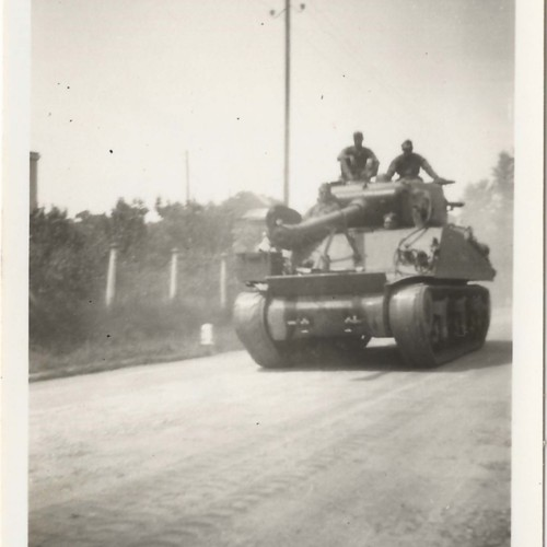 Tank on dirt road with soldiers atop vehicle