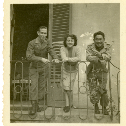 World War Two soldiers and a woman posing on a balcony