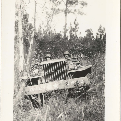 Two Japanese American soldiers in military truck in woods