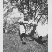 Takeshi Shindo sitting on a grassy hill in his uniform