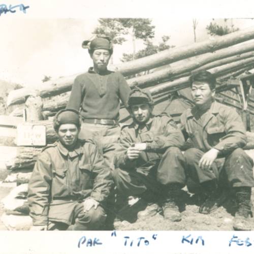 Soldiers in front of log cabin