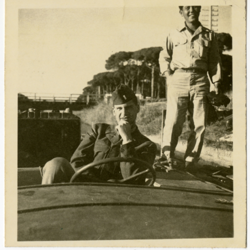 World War Two soldiers posing by a boat