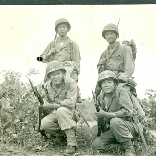 Four soldiers posing with guns