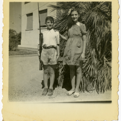 Boy and girl posing with a gun outside