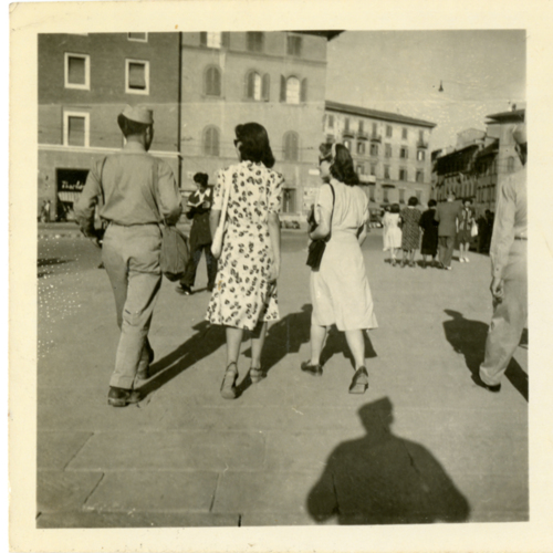 World War Two soldier walking with women in a piazza