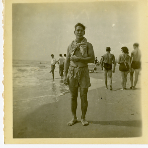 Man in bathing suit posing at the beach