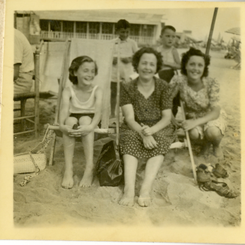 Women and children posing in beach chairs