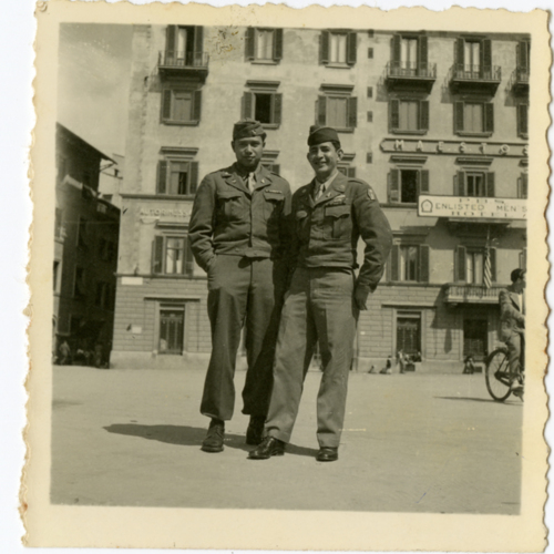 World War Two soldiers posing outside of a hotel