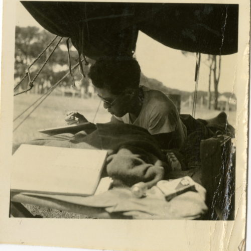 World War Two soldier writing outside in tent