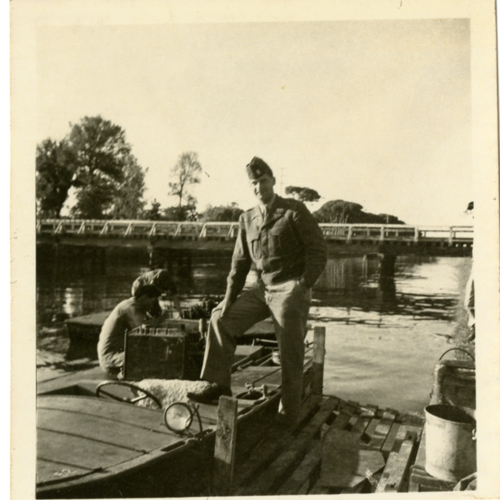 World War Two soldiers posing by and working on a boat