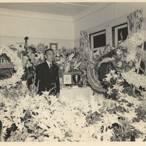 Funeral parlor for Sadamu Koito. Man standing in masses of floral arrangements