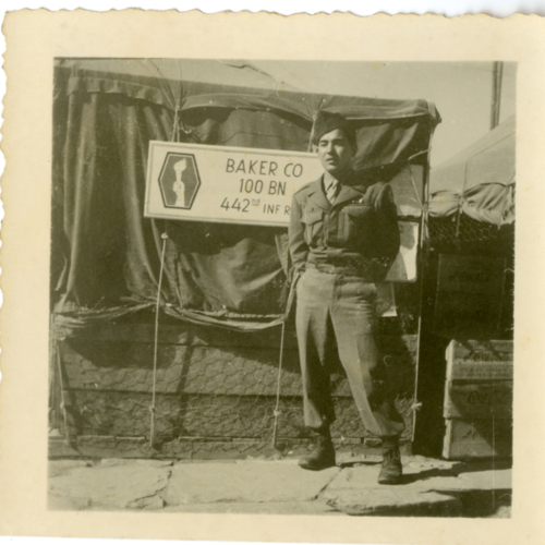 Paul William Nishimuta posing in front of a tent with a sign for the 442nd Regimental Combat Team, 100th Infantry Battalion, Baker Company