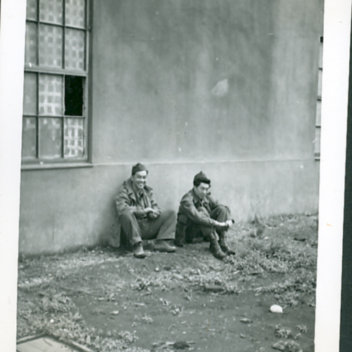 Two soldiers sitting against a wall