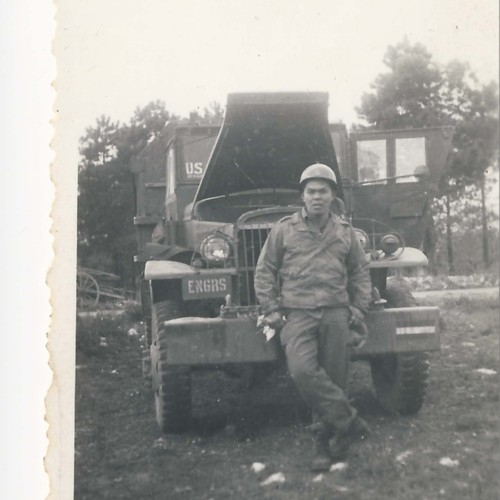 Japanese American soldier with helmet in front of Army truck