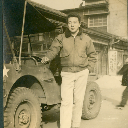 George posing in front of a jeep
