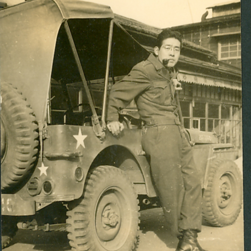 Soldier with pipe in front of jeep