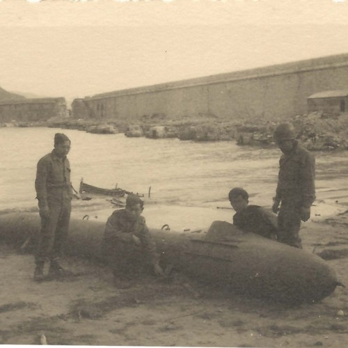Japanese American soldiers with torpedo on a beach