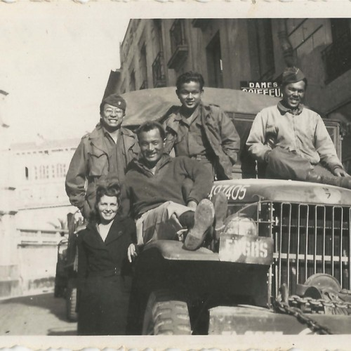 Japanse American soldiers sitting on truck with woman